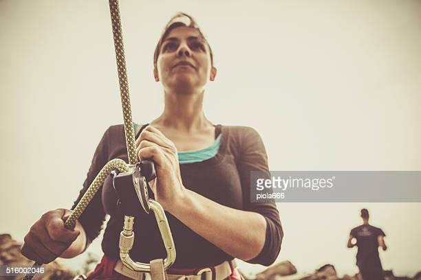 Girl securing rock climber while freeclimbing