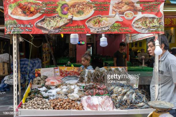 Girl seen by her seafood cart in Chinatown, Bangkok, Thailand. Daily life in Bangkok capital of Thailand.