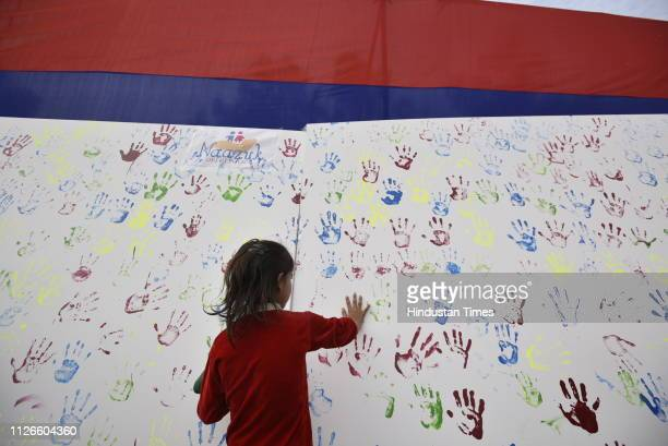 A girl seen putting her handprint over an installation during an awareness campaign program initiated by Delhi Police for those children who were...