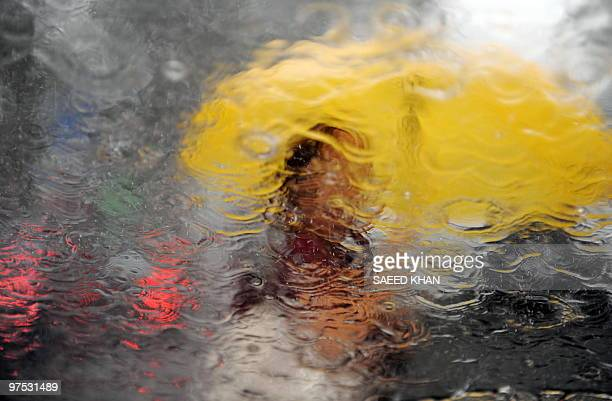 A girl seen through the windscreen of a holds an umberalla during a heavy downpour in town Kuala Lumpur on March 4 2010 AFP PHOTO / Saeed Khan