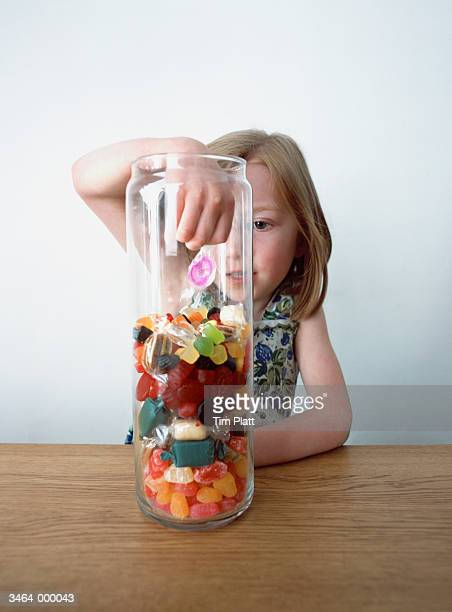 Girl Selecting Sweets from Jar