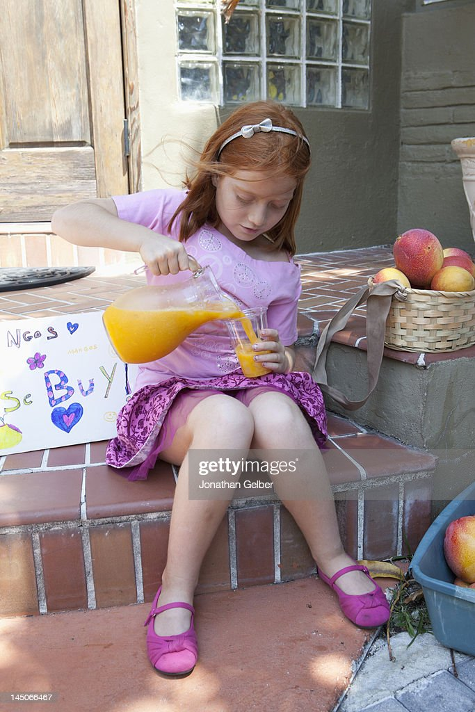 Girl selling apples on front porch and pouring juice from jug : Stock Photo