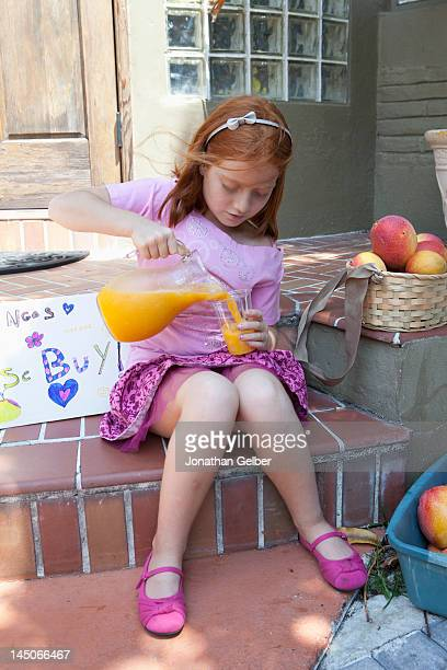 girl selling apples on front porch and pouring juice from jug - little girls up skirt fotografías e imágenes de stock