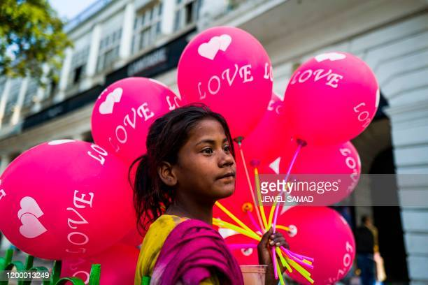 A girl selling balloons waits for customers ahead of Valentine's Day in New Delhi on February 11 2020