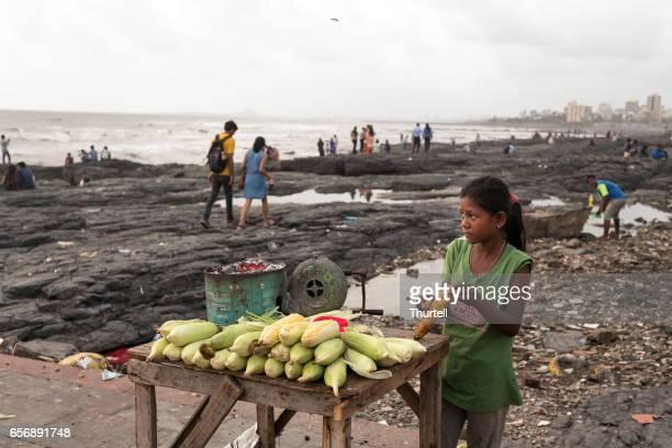 girl selling corn cobs on mumbai beachfront, mumbai, india - indian slums stock pictures, royalty-free photos & images