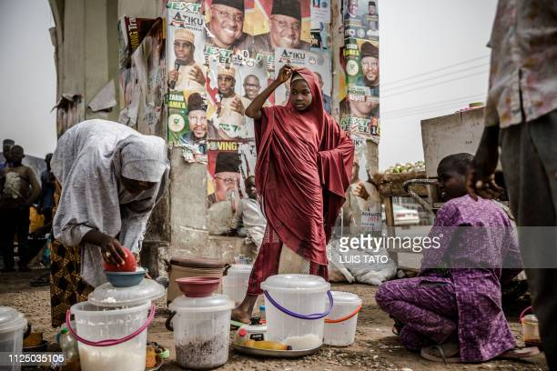 TOPSHOT A girl selling food waits for costumers in front of electoral posters in the Nigerian city of Mubi Adamawa State on February 15 on the eve of...