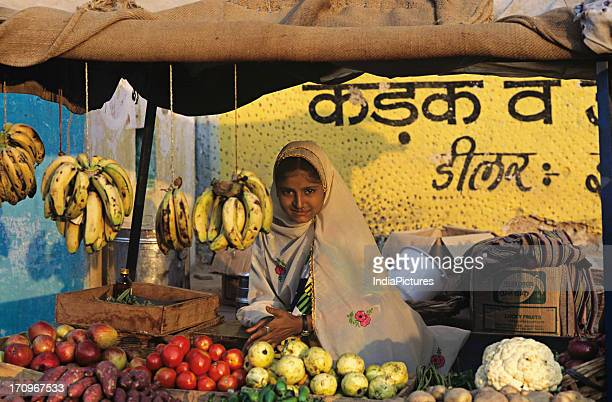 A girl selling fresh fruit and vegetables from a covered street stall Fatehpur Rajasthan India