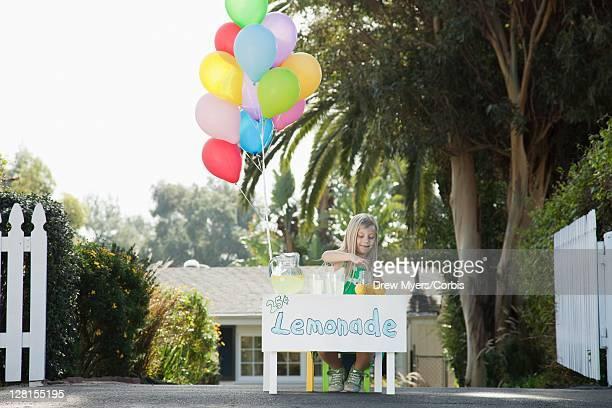 Girl (5-6) selling lemonade in front of house
