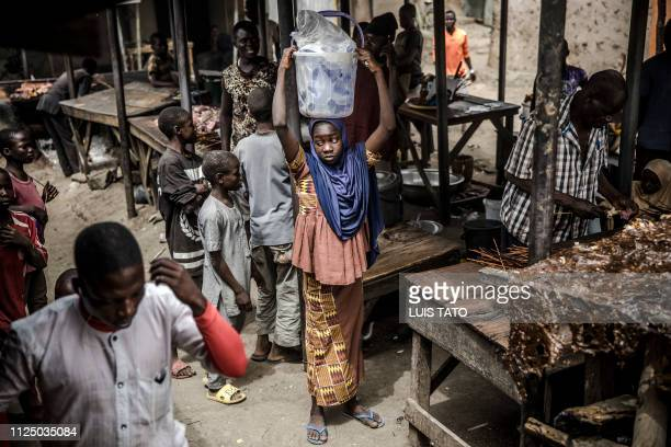 A girl selling water waits for costumers at a market which was attacked last year by Boko Haram Islamists in the Nigerian city of Mubi Adamawa State...