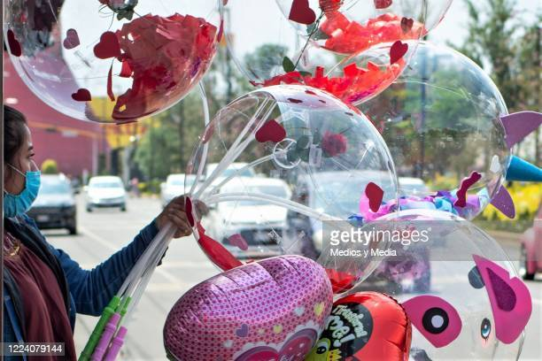 A girl sells balloons with messages and decoration inside on Avenida Pantitlan during Mother's Day in Nezahualcoyotl on May 10 2020 in State of...