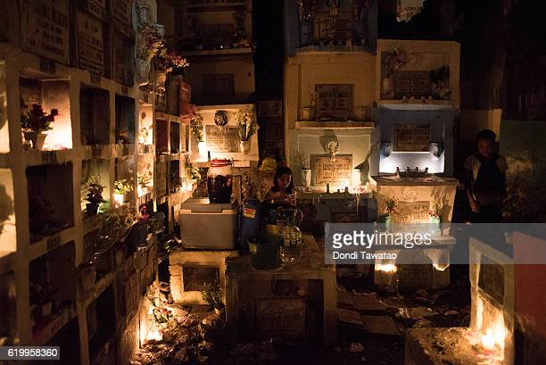 A girl sells refreshments inside a cramped public cemetery on November 1 2016 in Manila Philippines as Filipinos flock to cemeteries around the...