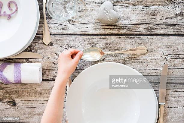 Girl setting a table, hand with spoon