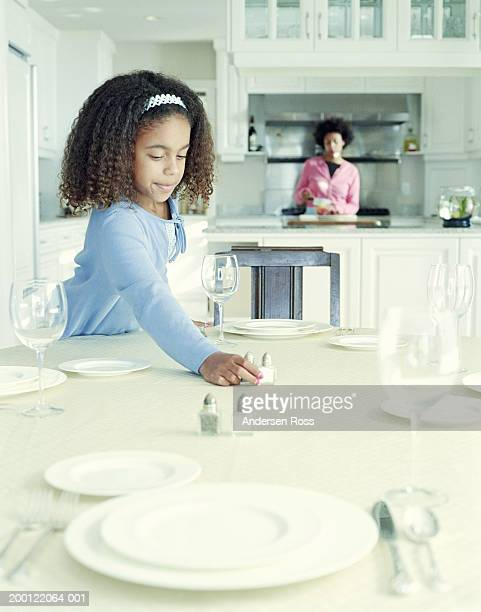 Girl (6-8) setting table, mother preparing food in background