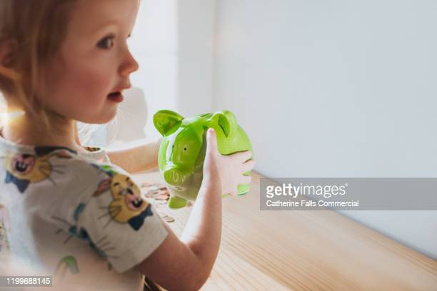 girl shaking piggy bank - charity benefit stock pictures, royalty-free photos & images
