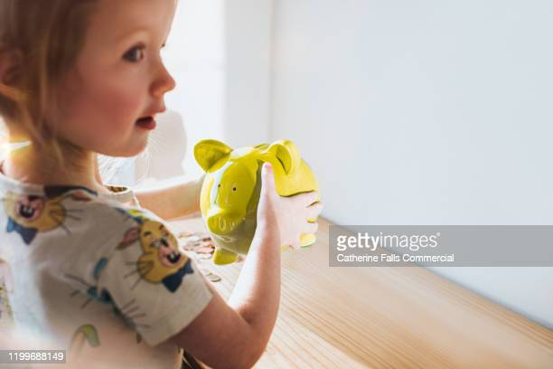 girl shaking piggy bank - british currency stock pictures, royalty-free photos & images