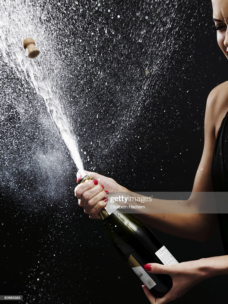 Girl shaking up bottle of champagne : Stock Photo