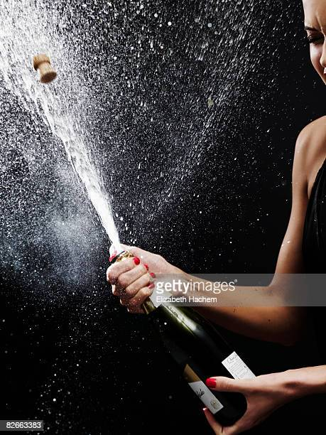 girl shaking up bottle of champagne - champagne stock pictures, royalty-free photos & images