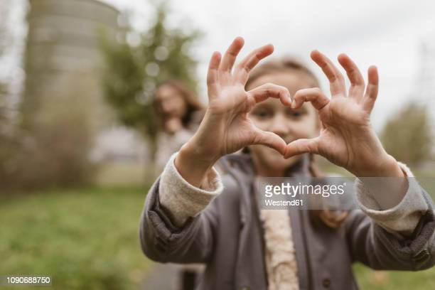 girl shaping hands to a heart - heart shape stock pictures, royalty-free photos & images