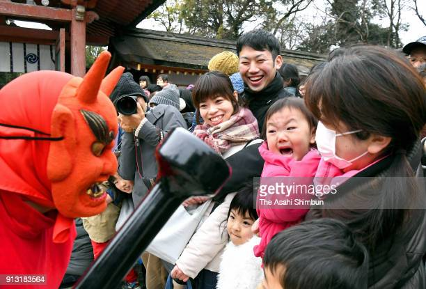 A girl sheds tears as a man wearing ogre mask approaches during the Oniyarai ritual socalled beanscattering at Iwashimizu Hachimangu Shrine ahead of...