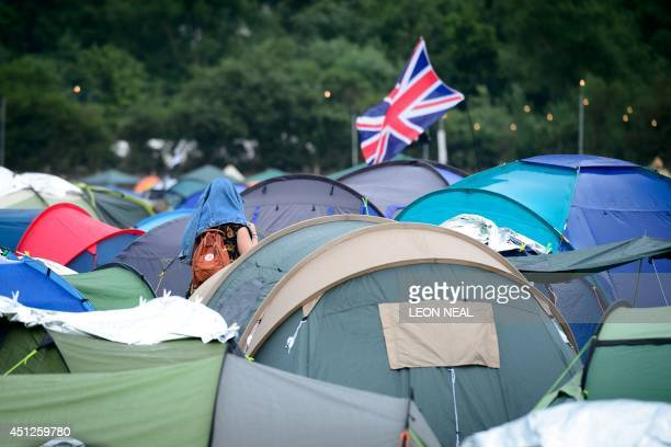 A girl shelters from the rain among the tents during the first rain showers as revellers gather ahead of the Glastonbury Festival of Music and...