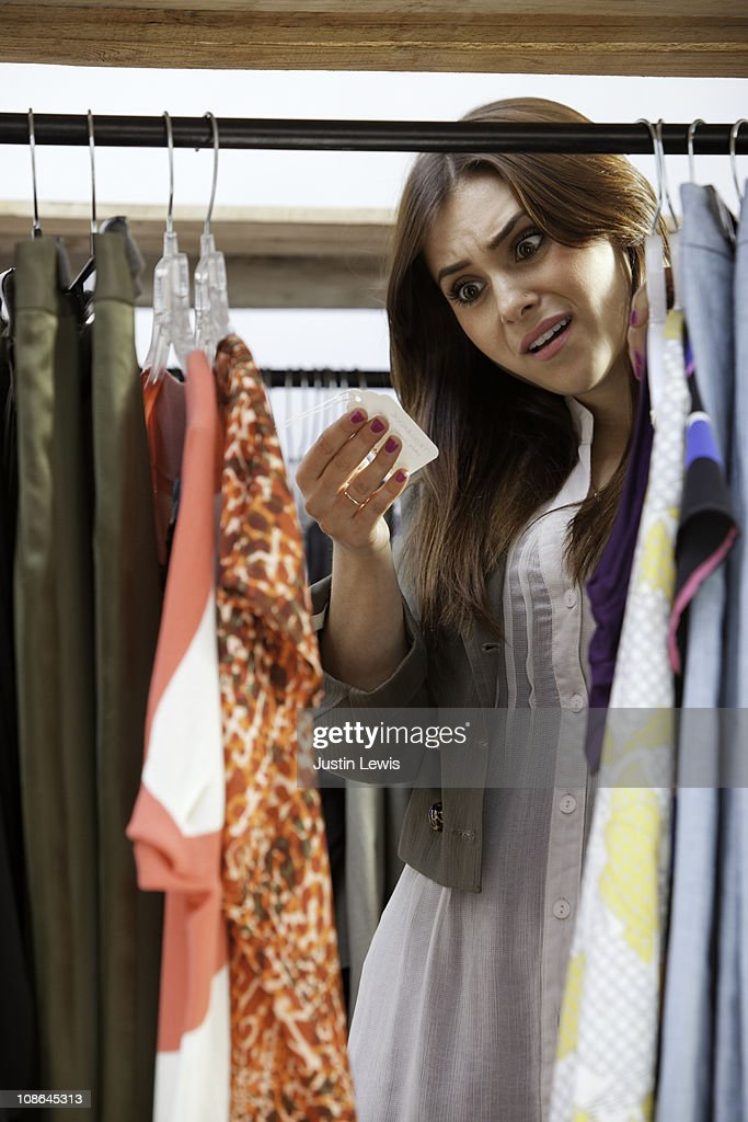 Girl shoked at the price of a clothing article : Bildbanksbilder