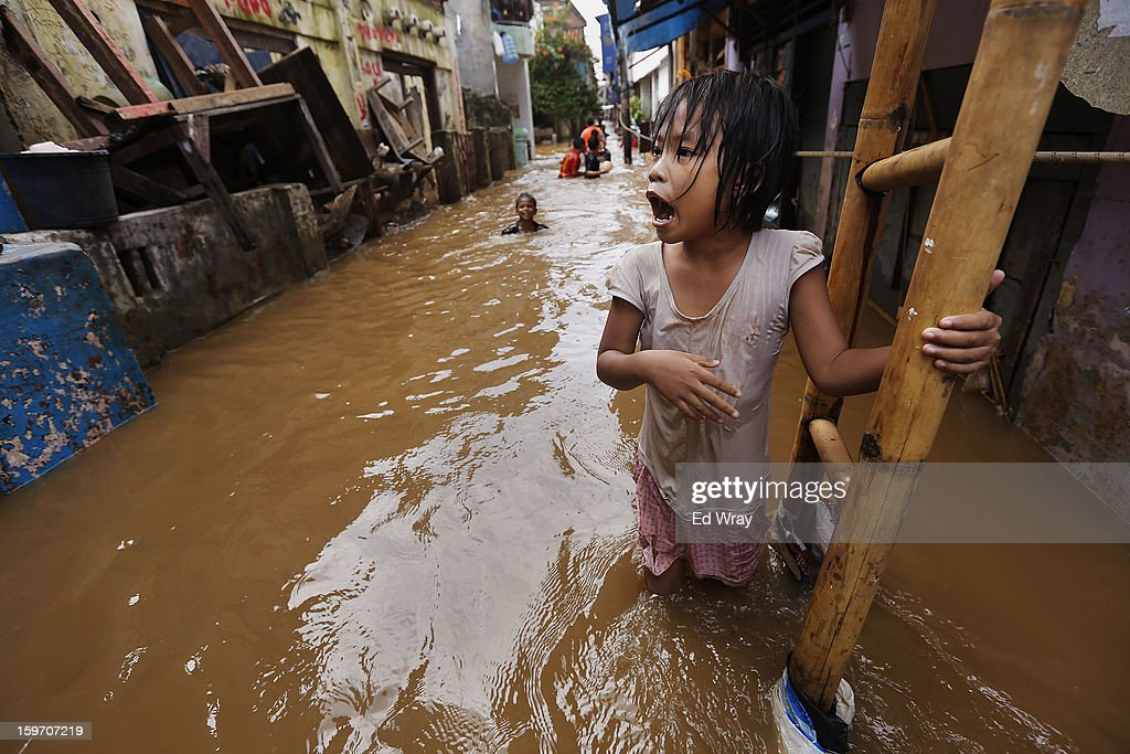 A girl shouts to a neighbour in front of her flooded house on January 19, 2013 in Jakarta, Indonesia. Floodwaters receded today after three days of heavy flooding which left thousands of people's homes underwater. According to Indonesian police the death toll has reached 15.