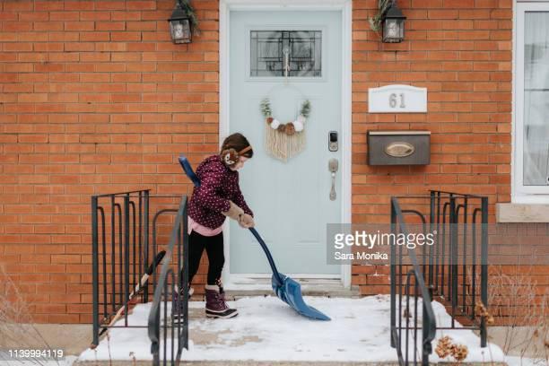 girl shovelling snow on porch - bottines photos et images de collection
