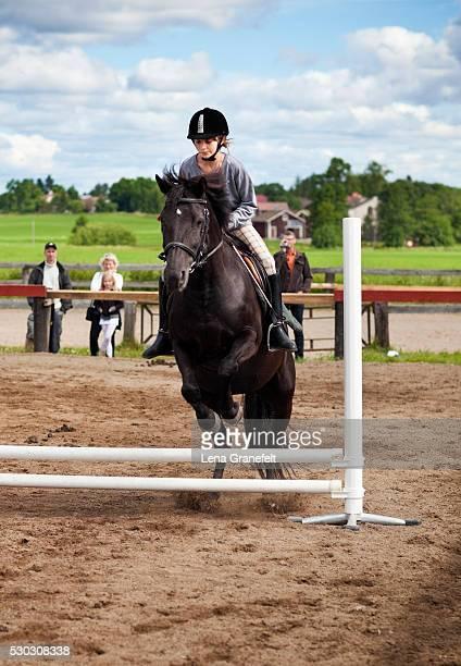 a girl show jumping - mensen op de achtergrond stockfoto's en -beelden