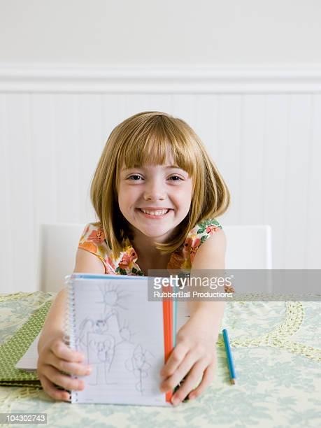 Chica mostrando un dibujo presentó