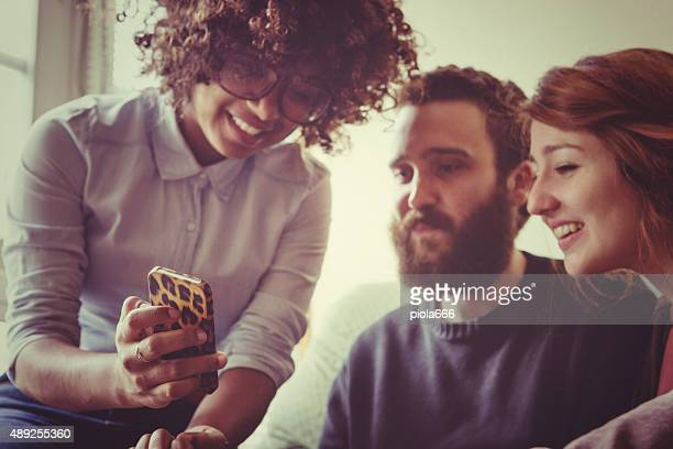 Girl showing a picture on her mobile phone to friends