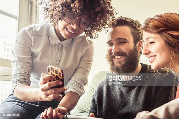 Girl showing a picture on her smartphone to friends