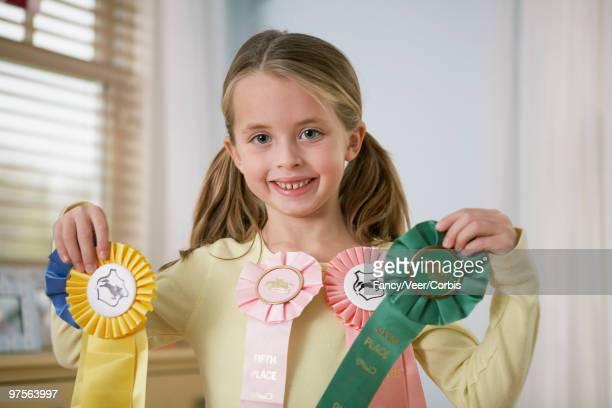 Girl showing award ribbons