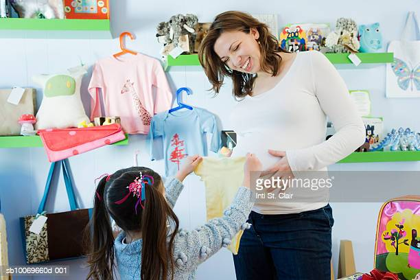girl (4-5 years) showing baby clothes to pregnant mother in children's boutique - 25 29 years stock pictures, royalty-free photos & images