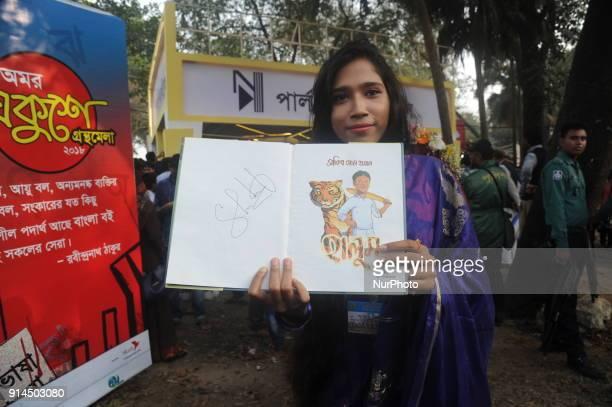 A girl showing Cricketer Shakib Al Hasan written a book name is quotHalumquot after buy in Ekushey Book Fair in Dhaka Bangladesh On February 5 2018
