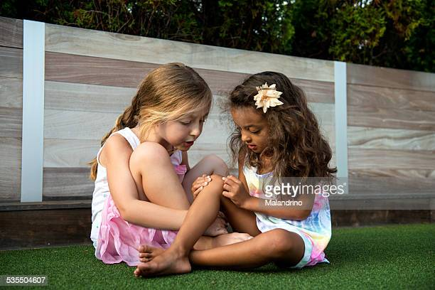 Girl showing her Boo Boo to her friend