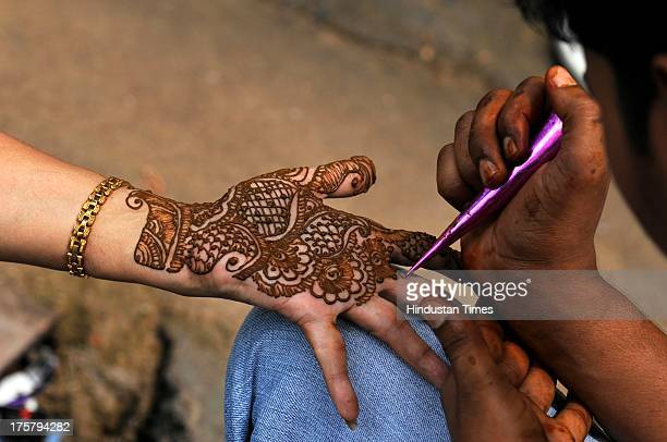 A girl showing her hands decorated with henna ahead of EidulFitr on August 8 2013 in Noida India Markets across the Muslim world witness huge...