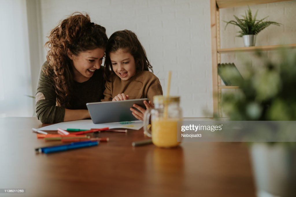 Girl showing her mom new games on her tablet. Sitting at table, taking a break from doing homework. : Stock Photo