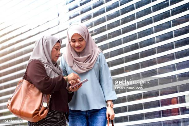 A girl showing her mother information on smart phone