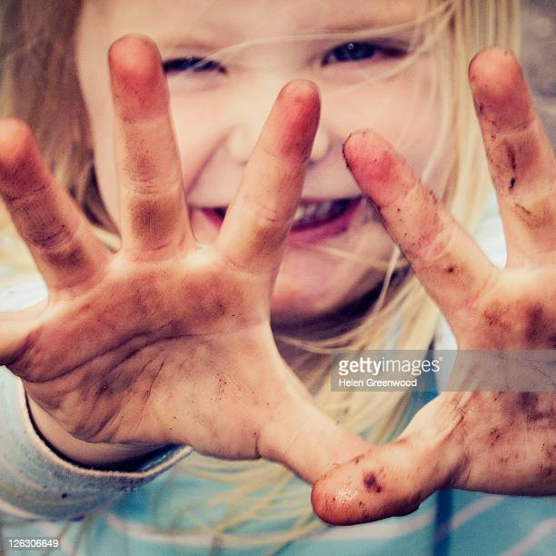 Girl showing her muddy hands