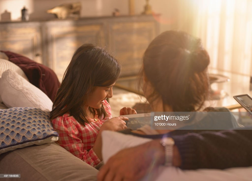 A girl showing her parents something on an iPad : Stock Photo