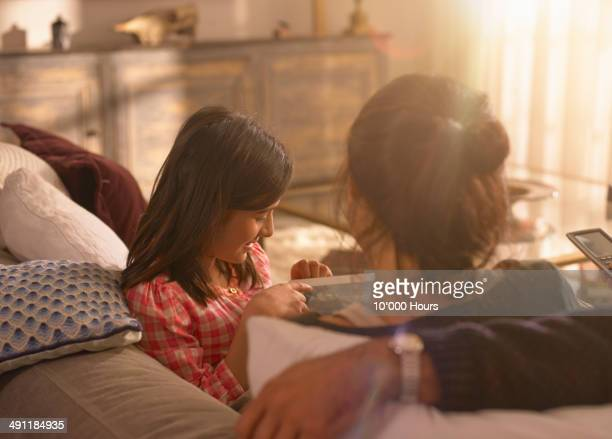 a girl showing her parents something on an ipad - indian couples stock pictures, royalty-free photos & images