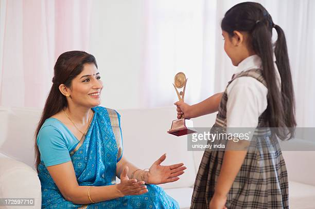 Girl showing her winning trophy to her mother