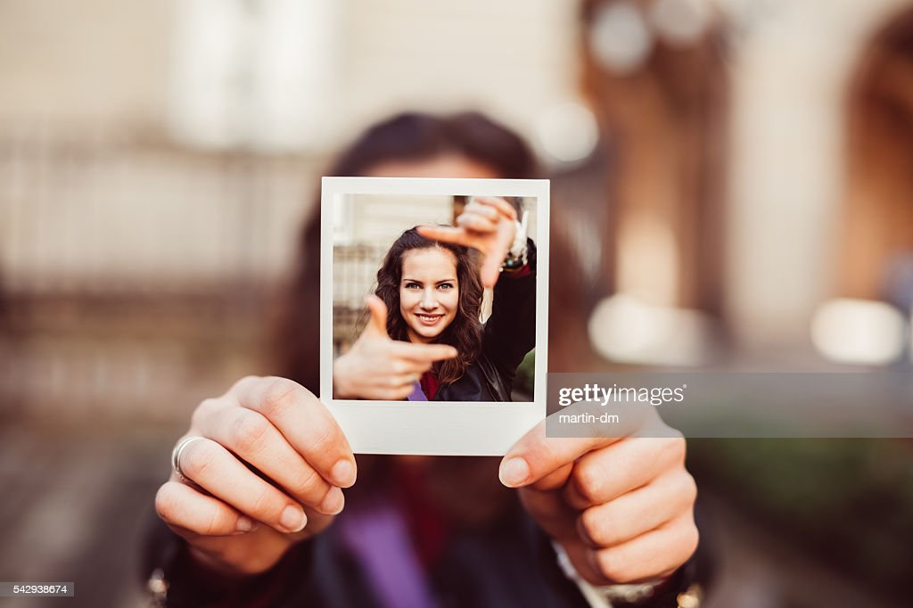Girl showing instant photo of hand framing concept : Stock Photo
