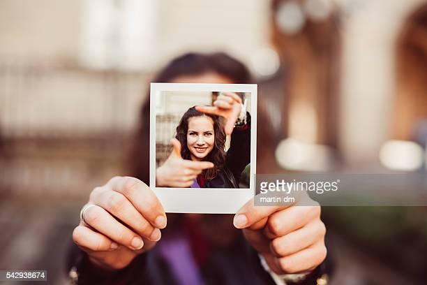 Mädchen mit sofortig Fotos von hand Rahmung Konzept