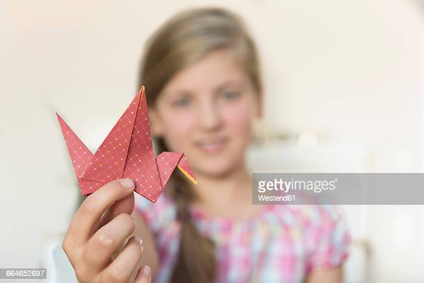 Girl showing origami bird
