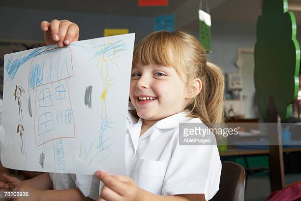 Girl (5-7) showing picture in classroom