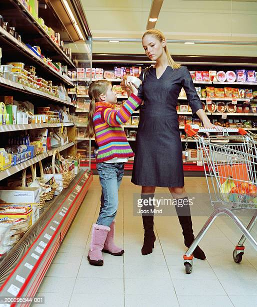 Girl (8-10) showing product to young woman in supermarket