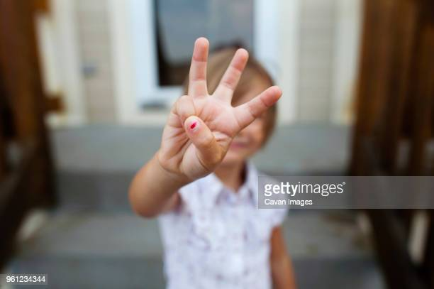 Girl showing three fingers while standing on steps