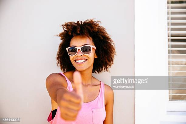 Girl showing thumbs up, close up