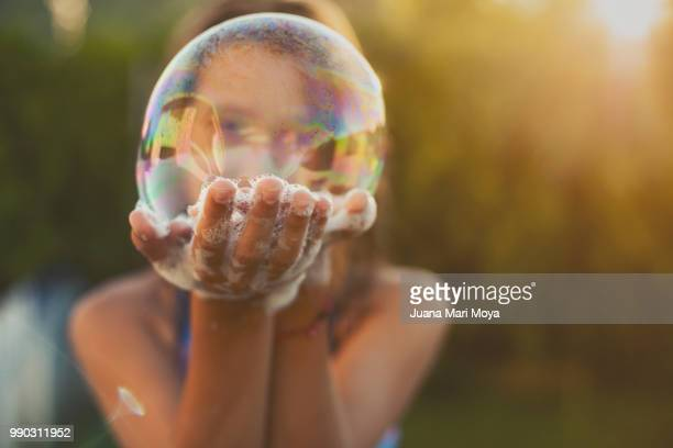 Girl shows a big bubble of soap on her hands.